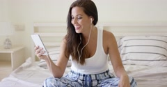 Happy woman listening with ear buds and tablet Stock Footage