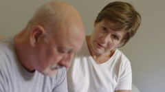 Older woman consoling older man - stock footage