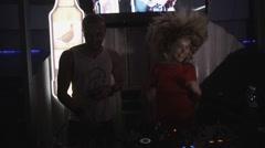 Dj girl in red dress shake hair at turntable in nightclub. Jump. Mc man. Party Stock Footage