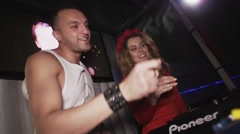Dj girl in red dress clap in hands at turntable in nightclub. Mc man. Dancing - stock footage