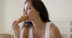 Woman eating fresh baked croissant in the bed - stock footage