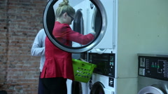 Couple are setting a clothes to the washing machine in a laundry - stock footage