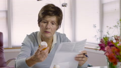 Senior woman reading prescription drug instructions Stock Footage