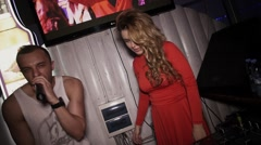 Dj girl in red dress dance at turntable in nightclub with mc man. Look in camera Stock Footage