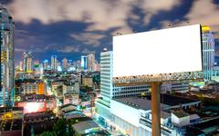Blank billboard for advertisement in city downtown at night Stock Photos