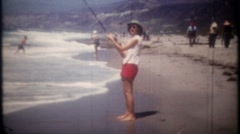 3458 woman fishing, casting long rod from the oceanshore-vintage film home movie Stock Footage