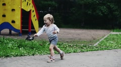 Little boy in shorts run to doves. Birds fly away. Summer park. Happiness - stock footage