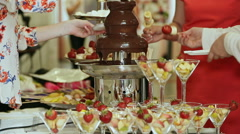 People dipped strawberries in chocolate fountain. Celebration Stock Footage