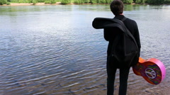 Man walks edge of river with acoustic guitar seeking inspiration for songwriting - stock footage