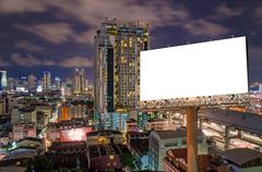 Blank billboard for advertisement in city downtown at night - stock photo