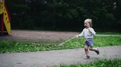 Blonde little boy run on playground to mother. Doves in summer park. Childhood - stock footage