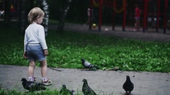 Blonde little boy running on playground in summer park. Childhood. Flying doves - stock footage