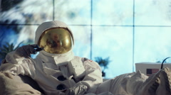 4K Astronaut in full suit relaxing in apartment, watching TV & channel surfing Stock Footage