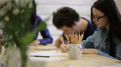 A group of young men and women sitting at table and drawing courses painting Stock Footage