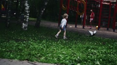 Blonde little boy running on playground in summer park scare doves. Kids - stock footage