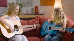 Two girls on a couch playing guitars Stock Footage