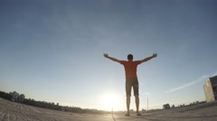 Man with arms outstretched towards the sun on the roof Stock Footage