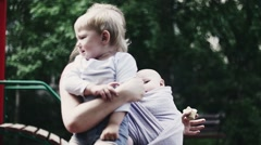 Mother with baby hold little crying boy on hands on playground. Family. Summer Stock Footage