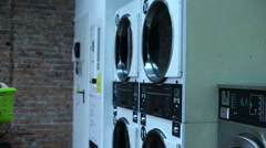 Woman with baby is setting a clothes to the washing machine in a laundry - stock footage