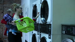 Mother with baby is setting a clothes to the washing machine in a laundry - stock footage
