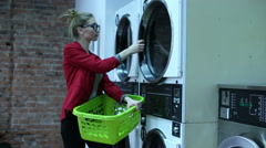 Young woman is setting a clothes to the washing machine in a laundry Stock Footage