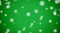 Snowflakes Fall Against a Green Background Stock Footage