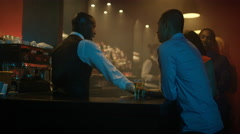 4K Friendly bar staff serving drinks & chatting to customers in city bar Stock Footage