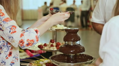 People dipped strawberries in chocolate fountain Stock Footage