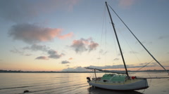 sailboat on its side in outgoing tide at sunset - stock footage
