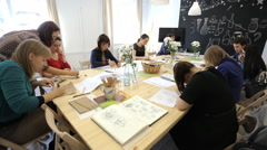 People sit around wooden table in art studio on seminar - stock footage