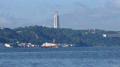 Ferry passing bij at 25 de Abril brigde on Tajo river - stock footage
