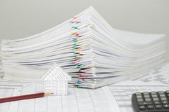 House and pencil with blur pile overload paperwork Stock Photos