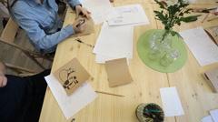 Brunette in denim shirt paints figures of glasswares Stock Footage