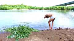 Man washes his face in mountain creek or river Stock Footage