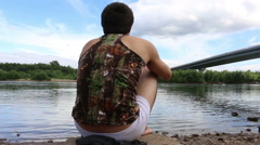 A man sits opposite the river, meditates and smokes. in the background of the Stock Footage