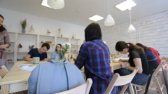 Light blue backpack lies on wooden chair in art studio Stock Footage