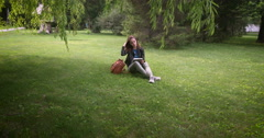 Girl sitting in the park with a computer Stock Footage