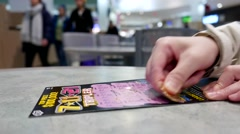 Scratching lottery ticket inside shopping mall food court area - stock footage