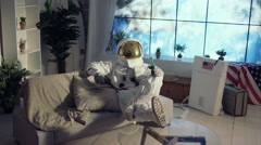 4K Astronaut relaxing in apartment, watching TV & drinking a beer Stock Footage