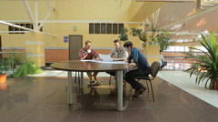 Three young architects sit at round wooden table and look at graphic Stock Footage