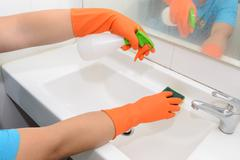 Man doing chores in bathroom at home, cleaning sink and faucet with spray det Stock Photos