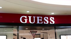 Motion of Guess store sign on wall inside shopping mall Stock Footage