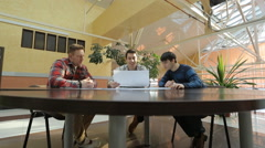 Engineers sit at round wooden table and discuss project Stock Footage