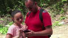 Hikers - hiking family looking at map using GPS to navigate during camping tr Stock Footage