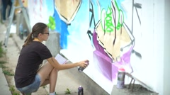 Young graffiti artists. Girl artist paints a picture of a concrete fence Stock Footage