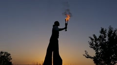 Fantastic Show at Sunset. Circus on Stilts Spit the Fire. Slow Motion. Stock Footage