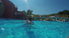 Young kids jumping in to the pool from father's legs, Slow motion Stock Footage