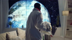 4K Astronaut in apartment with view of planet earth getting ready for a mission Stock Footage