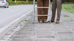 Senior woman using a walker cross street with assistance. Stock Footage