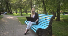 Girl with a laptop on a bench in the park - stock footage